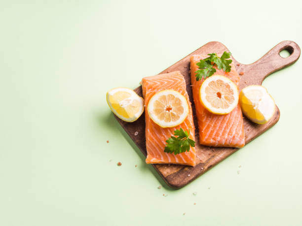 Salmon fillet on wooden board with lemon slices stock photo