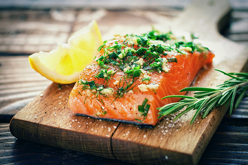Raw salmon on a cutting board with fresh spices