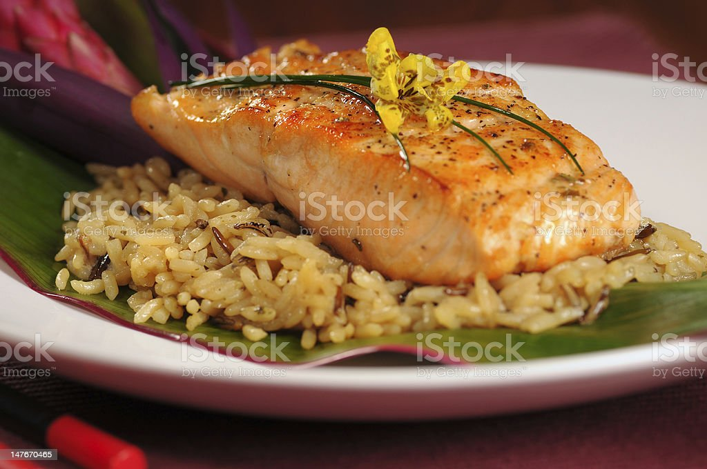 Salmon fillet served over a bed of rice on a banana leaf royalty-free stock photo