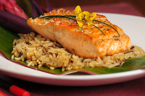 Salmon fillet served over a bed of rice on a banana leaf stock photo