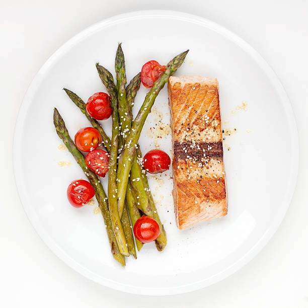 Salmon fillet with asparagus and cherry tomatoes stock photo