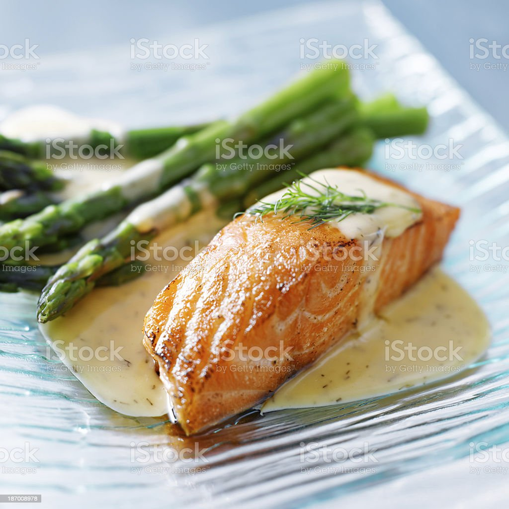 Salmon fillet with asparagus and yellow sauce stock photo