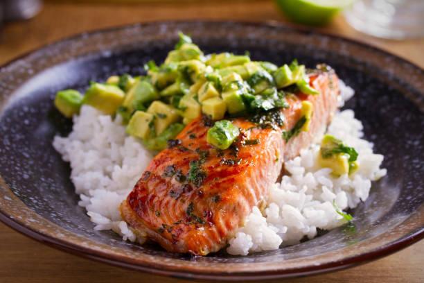 lachsfilet mit avocado limetten-koriander-salsa, reis als beilage - steak anbraten stock-fotos und bilder