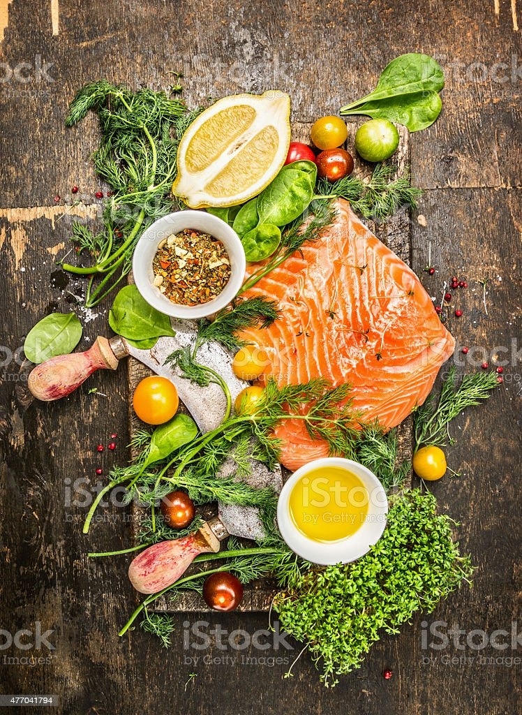 Salmon fillet with fresh healthy herbs,vegetables, oil and spices stock photo