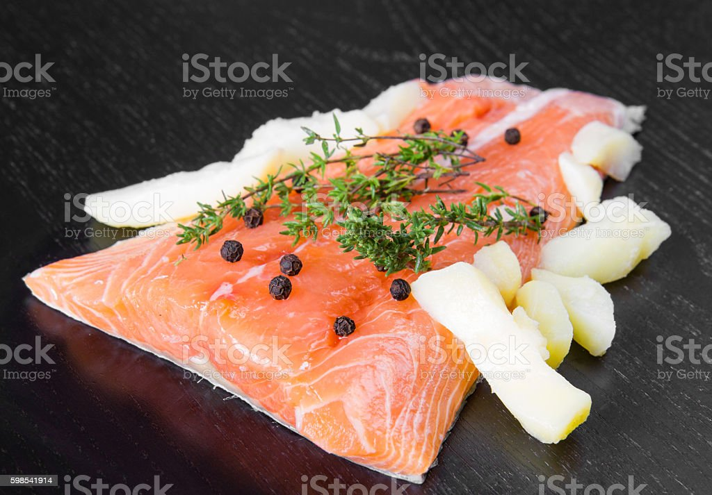 Salmon fillet with potatoes  isolated on black wood photo libre de droits
