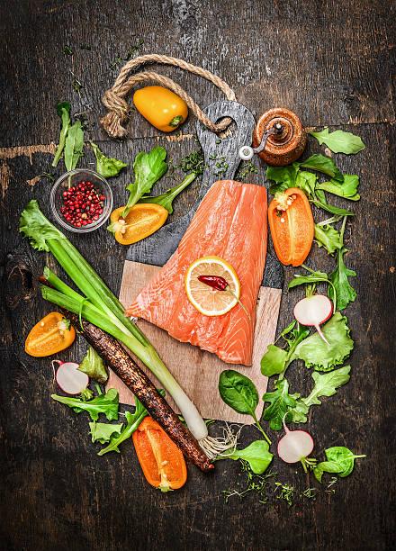 lachs-filets auf schneidebrett und gemüse und gewürzen zubereitet - schwarzwurzeln kochen stock-fotos und bilder