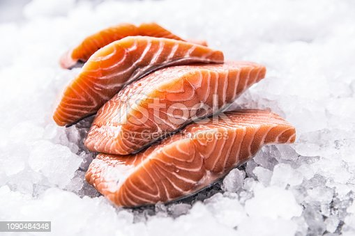 Salmon fillets portioned on ice and empty kitchen board.