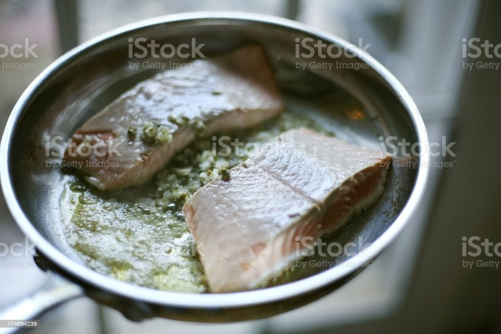 Salmon fillets sizzling in caper butter stock photo