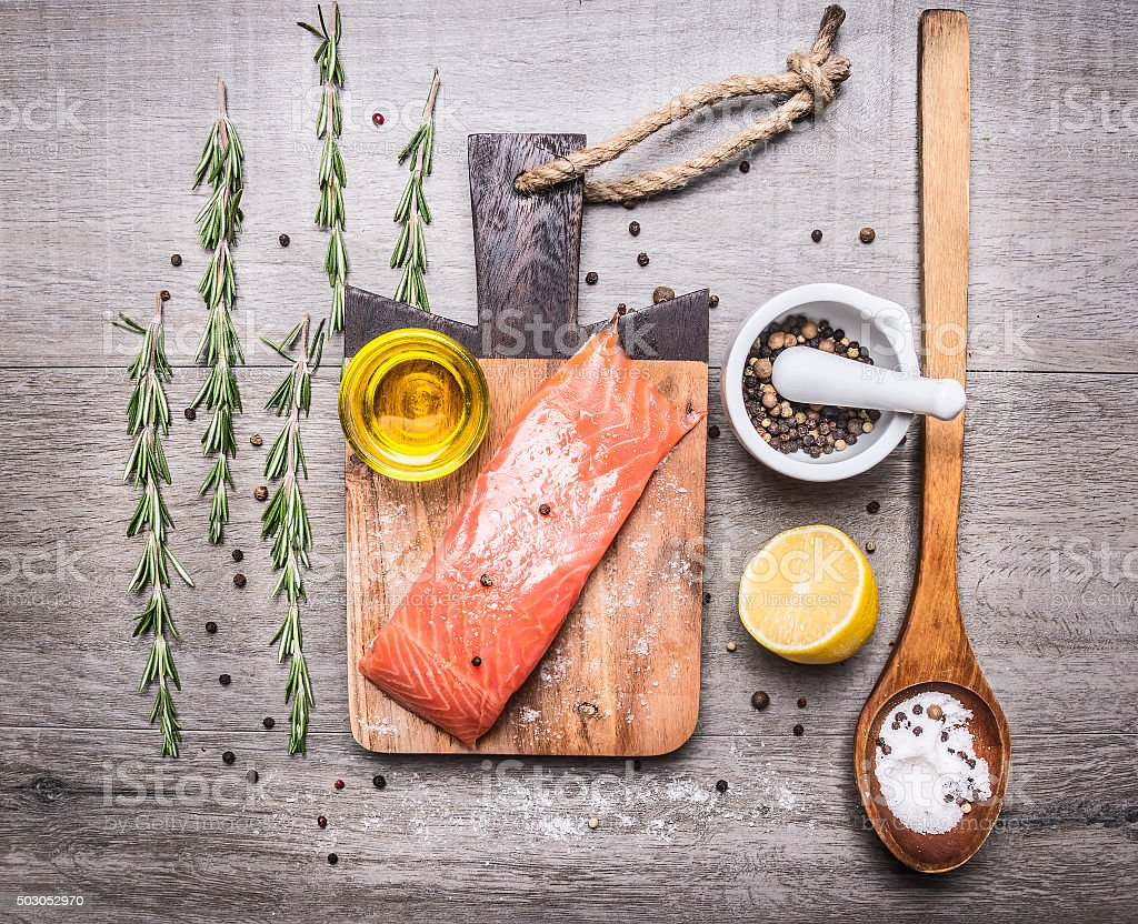 salmon fillets with oil, lemon, pepper, herbs  cutting board stock photo
