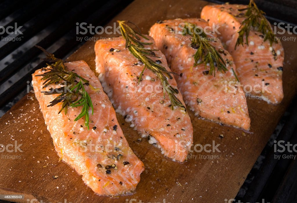 Salmon Fish Fillet Meat; Seafood Cooking on Barbeque Grill & Plank stock photo