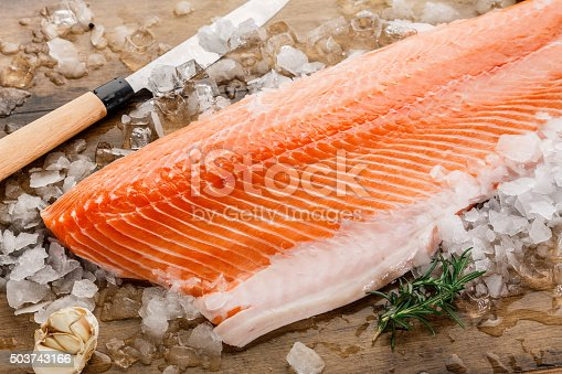 Salmon fish on ice on a wood table
