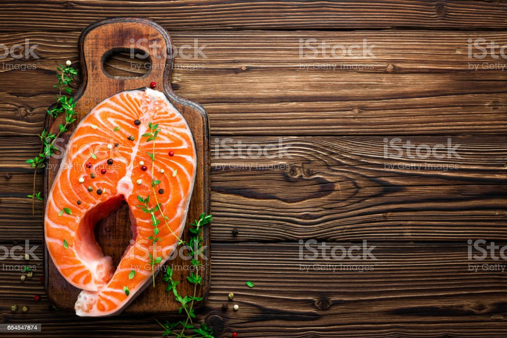 Salmon fish steak on black background copy space top view stock photo