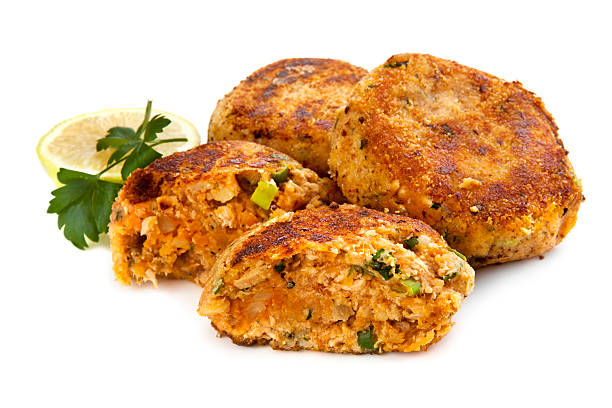 Salmon Fishcakes over White Background Salmon fishcakes or patties, with lemon and parsley, isolated on white background. tuna seafood stock pictures, royalty-free photos & images