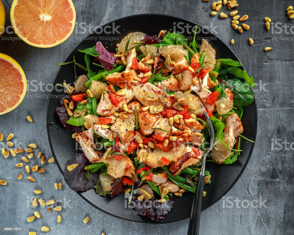 Salmon, green bean and pink grapefruit salad with balsamic vinegar drizzle and pine nuts stock photo