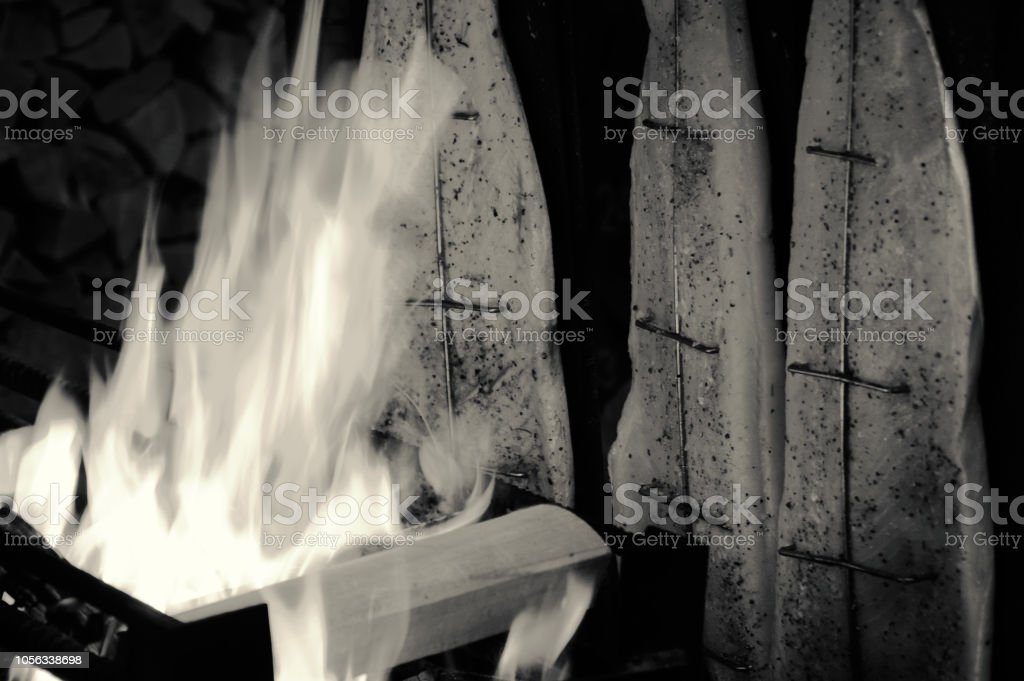 Salmon grilled in open fire rustic smokehouse. Black and white photo.