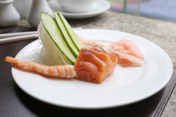 salmón de sashimi en el plato blanco en un restaurante. - pez sierra fotografías e imágenes de stock