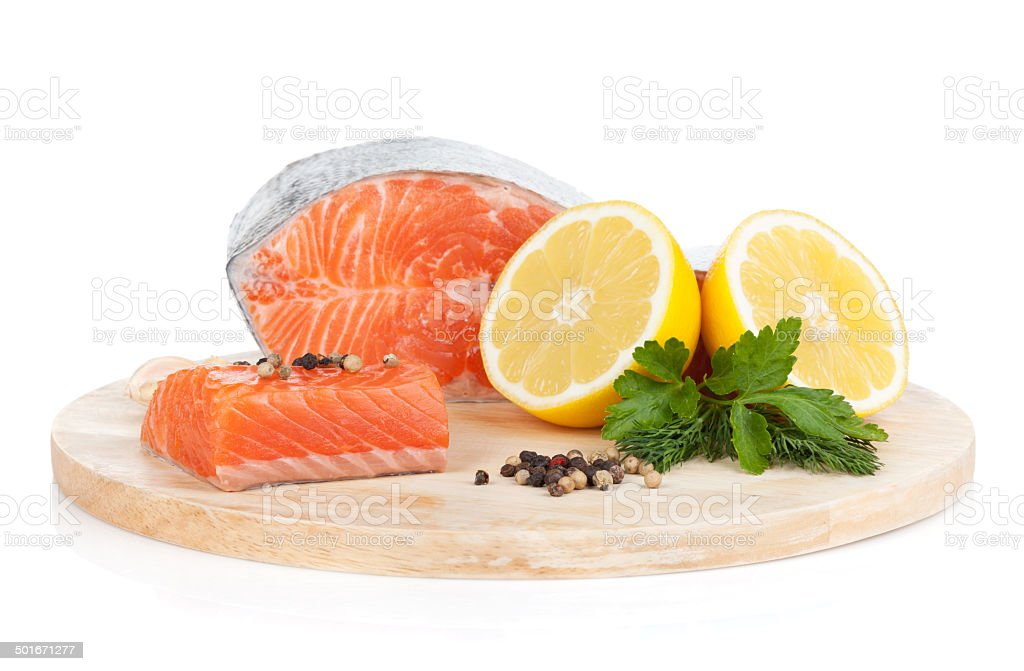 Salmon on cutting board with lemons and herbs stock photo