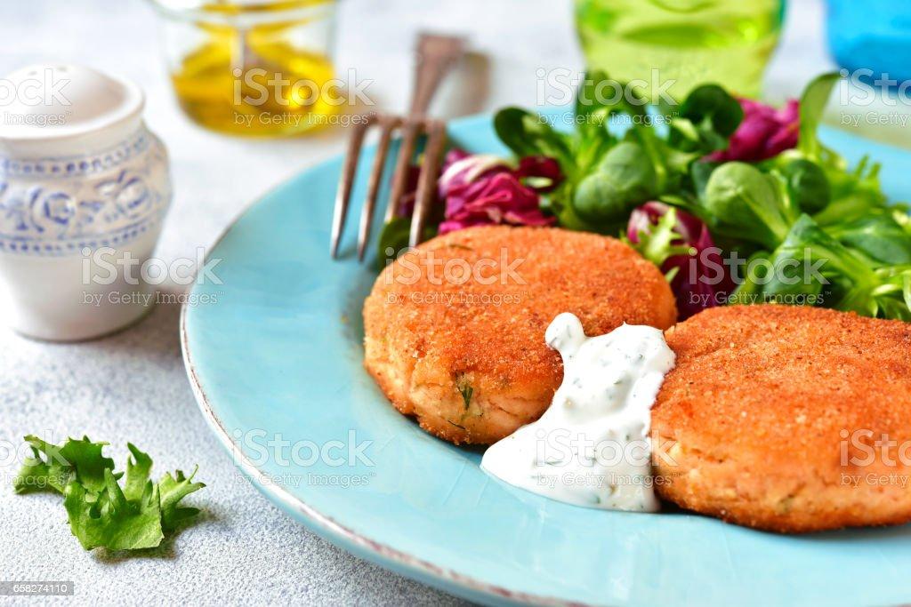 Salmon patties with mix salad leaves and yogurt sauce stock photo