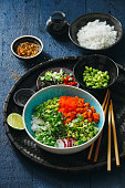 Poke bowls with salmon, tobiko red, avocado, edamame, vegetables, sprouts and rice on dark blue background
