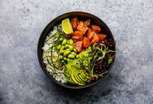 Salmon Poke bowl raw fish salad Asian trendy food with soy beans edamame, rice, avocado, tropical fruit and lettuce in bowl on gray background stock photo