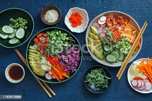 Poke bowls with salmon, tobiko caviar, avocado, edamame, vegetables, sprouts, microgreen and rice on dark blue background