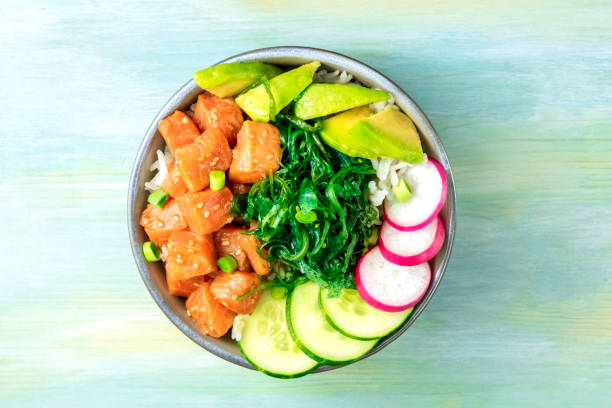 Salmon poke with avocado, wakame and cucumber, shot from above on a teal blue background with a place for text stock photo