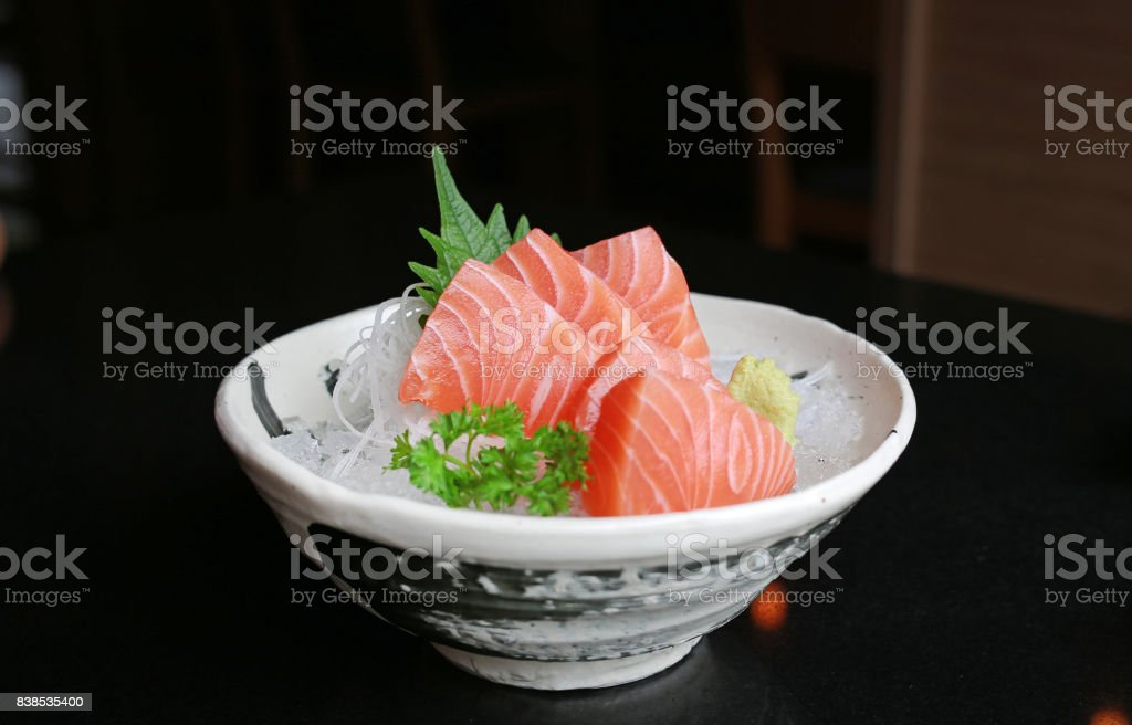 Salmon raw slice or salmon sashimi in Japanese style fresh serve on ice with fresh wasabi on black table stock photo