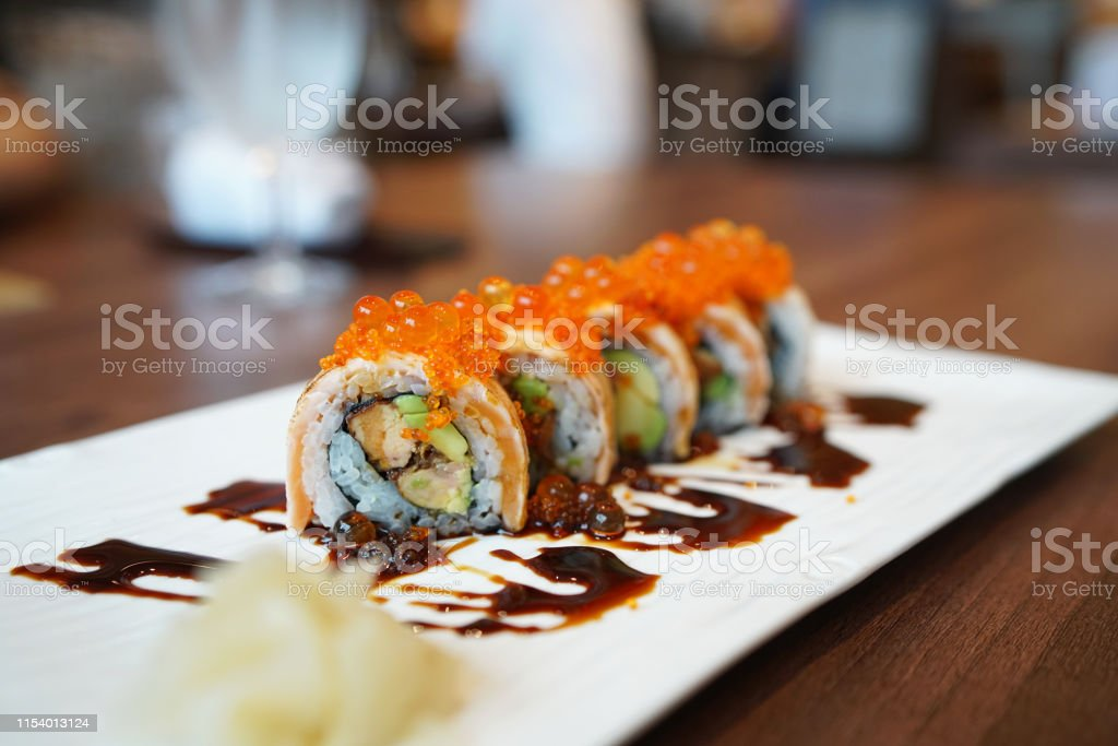 Salmon Roll A Plate Of Grilled Salmon Roll With Avocado And Foie Gras Topped With Ikura Roe And Sweet Sauce On Blurred Background Traditional Japanese Food Stock Photo Download Image Now