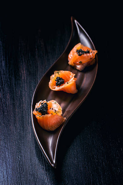 salmon rolls with black caviar - food styling stock photos and pictures