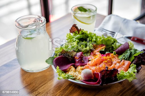 Smoked salmon salad on a wooden table top with silverware and white cloth napkin in a modern and casual setup.