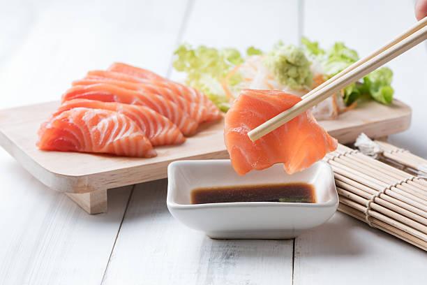 salmon sashimi  with chopsticks. - 熟した ストックフォトと画像