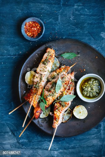 Salmon satay with pesto and chili sauce and herbs