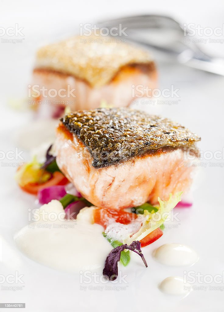 Salmon squares with crispy skin set on colorful vegetables stock photo