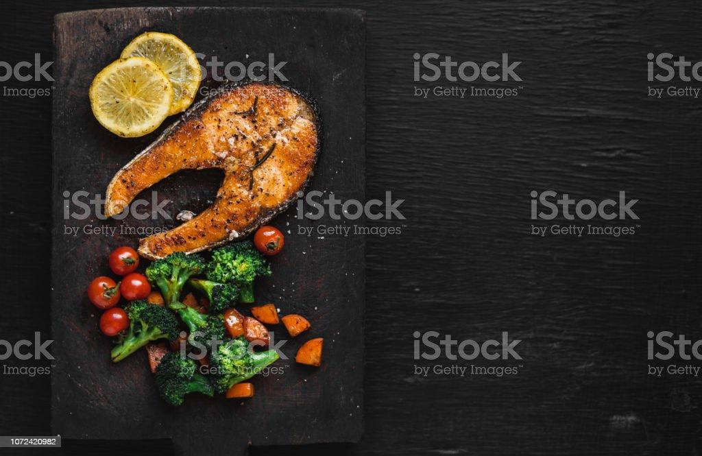 Lachs Steak und Gemüse auf schwarzem Holz hacken – Foto