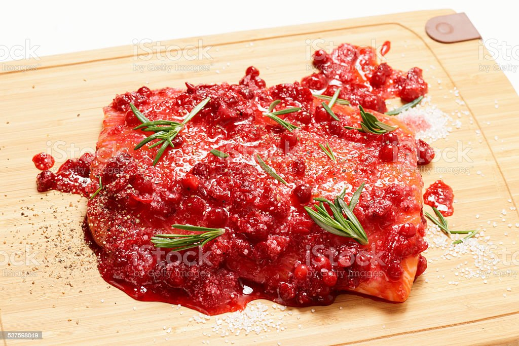 Salmon steak being marinated in salt with redberries stock photo