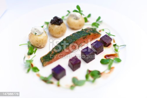 Salmon steak encrusted with parsley with beetroot cubes, salad and caviar