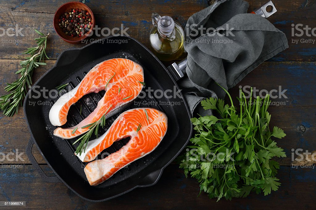 Salmon Steak on griddle pan and rosemary, parsley, spice stock photo