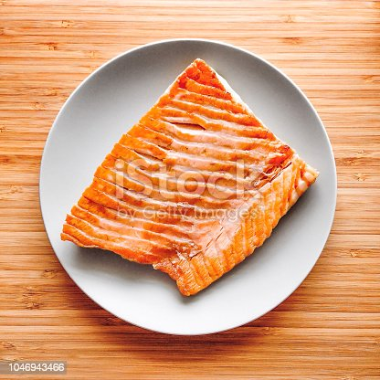 Roasted salmon steak on a wooden background, top view