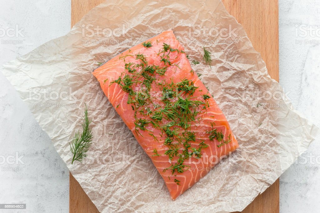 Salmon steak with dill and salt on a cooking paper. Gravlax. Top view. stock photo