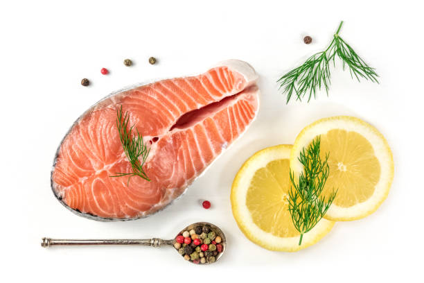 Salmon steak with lemons, dill, and peppercorns, on white An overhead photo of a raw salmon steak with dill, lemons, and peppercorns, shot from above on a white background with a place for text dill stock pictures, royalty-free photos & images