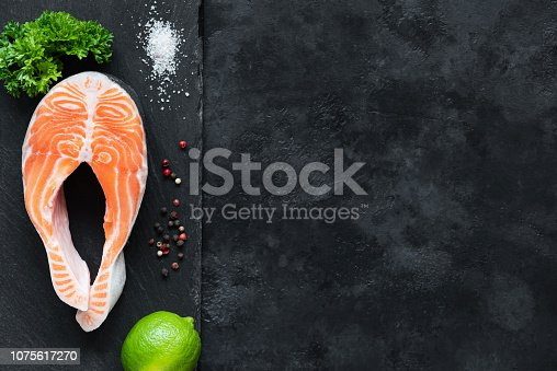 istock Salmon steak with lime on slate background ready for cooking 1075617270