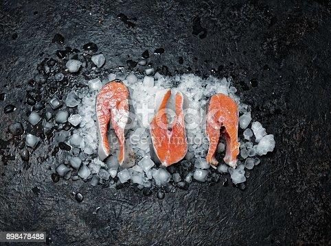 Fresh salmon steaks on ice over black background