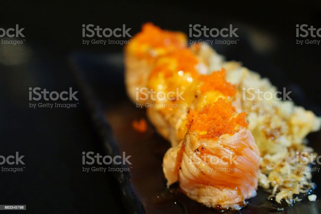 Salmon sushi roll topped with spicy mayonnaise sauce and ebiko roe (Capelin fish caviar) served with crunchy tempura flakes. stock photo