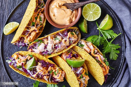 salmon tacos with red cabbage salad with spicy yogurt sauce sprinkled with finely chopped parsley served on a black plate on a dark wooden table, horizontal view from above, flat lay, close-up
