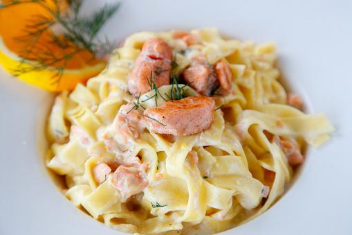 Salmon tagliatelle in cream sauce decorated with orange slice and dill