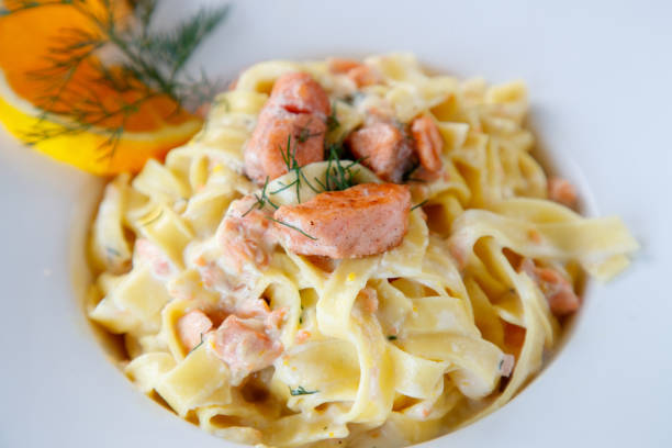 Salmon tagliatelle in cream sauce Salmon tagliatelle in cream sauce decorated with orange slice and dill tagliatelle stock pictures, royalty-free photos & images