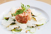 Salmon Tartar with sliced cheese, pesto sauce and basil on white plate.