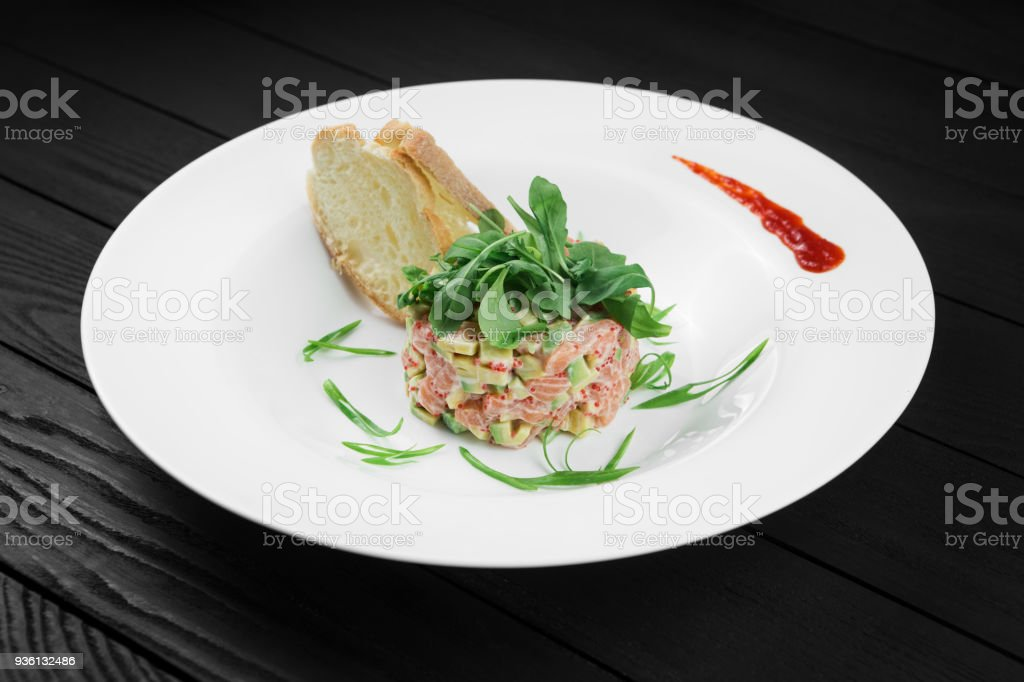 Salmon tartare with avocado on white plate. stock photo