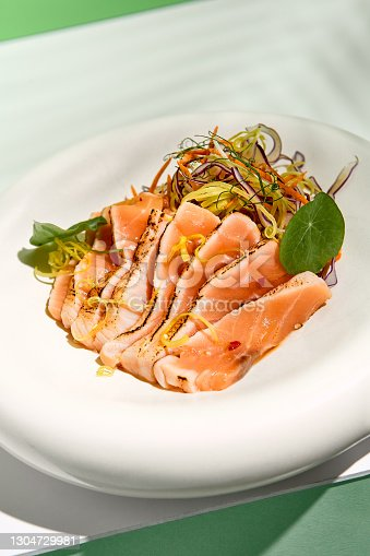 istock Salmon tataki in sesame with salad. Fish sashimi restaurant appetizer on white table with green wall. Day sunlight with hard shadow of tropical palm leaves. Summer or spring food concept. 1304729981