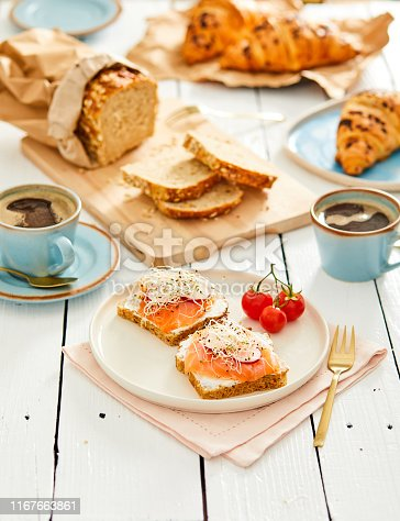 Healthy salmon toasts for breakfast, with bread, tomatoes and coffee in the background.